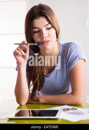 Jeune femme à la plume et l'ordinateur tablette, la réflexion et la résolution de problèmes, studio shot