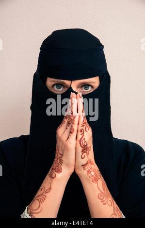 Portrait de femme en noir hijab musulman et musulmane robe, mains priant et peinte au henné en style arabe Banque D'Images