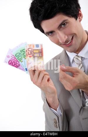 Homme d'affaires riche montrant outre de son argent Banque D'Images