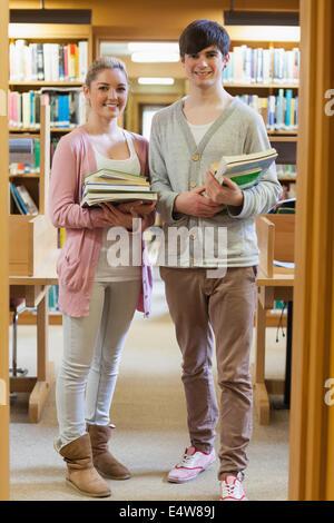 Couple debout à la bibliothèque holding books Banque D'Images