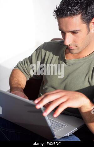 Homme aux cheveux noirs s'assit avec coffre