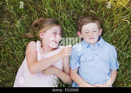 Deux enfants, frère et sœur se trouvant côte à côte sur l'herbe Banque D'Images
