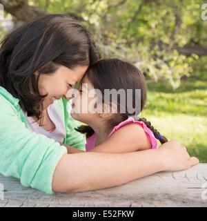 Une mère dans le parc avec sa fille, à rire et à s'embrasser. Banque D'Images