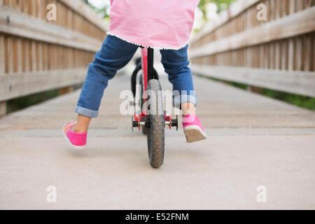 Un enfant à cheval sur un vélo sur un trottoir. Banque D'Images