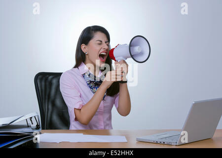 Frustrated businesswoman yelling in megaphone at office desk
