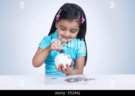 Smiling girl putting coins in piggy bank contre fond bleu Banque D'Images