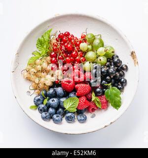 Mélange de baies fraîches avec des feuilles en céramique vintage passoire sur fond blanc Banque D'Images
