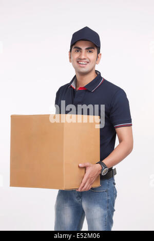 Portrait of handsome man carrying cardboard box against white background Banque D'Images