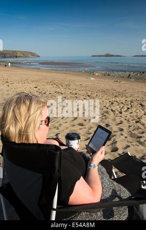 Royaume-uni, Pays de Galles, Gwynedd, péninsule de Lleyn, plage, Aberdaron, woman reading book ereader sur drinking Banque D'Images