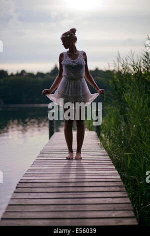 Jeune femme en robe blanche debout sur une passerelle sur le lac Banque D'Images