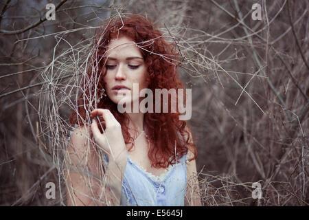 Femme aux longs cheveux rouges entre les branches, portrait Banque D'Images