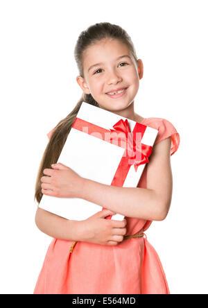 Smiling cute girl 8-9 ans tenant dans les mains de fête d'anniversaire. Isolé sur un fond blanc.