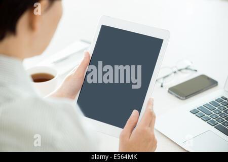 Personne d'affaires holding digital tablet moderne et à la recherche sur un écran vierge. Travail de bureau élégant Banque D'Images