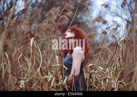 Femme aux longs cheveux rouges debout dans les roseaux, Portrait Banque D'Images
