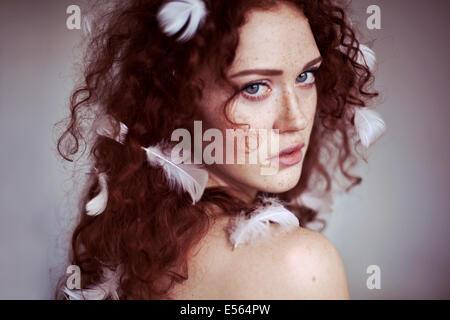 Jeune femme avec des plumes dans les cheveux Banque D'Images