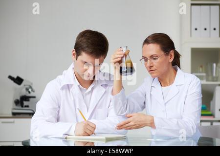 Deux scientifiques ce qui complique l'analyse de l'huile liquide dans la fiole à laboratory Banque D'Images