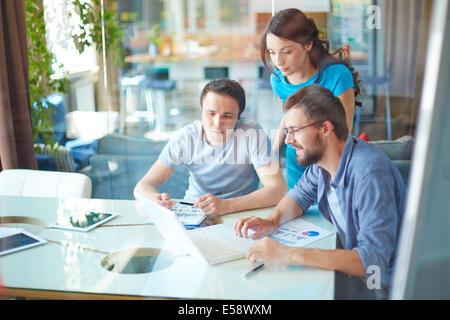 Groupe des trois partenaires d'affaires à l'aide d'occasionnels ordinateur portable à la réunion in office Banque D'Images