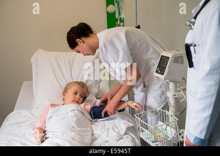 Personnel médical l'examen de la pression artérielle d'un patient fille in hospital bed Banque D'Images