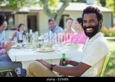 Man smiling at table outdoors Banque D'Images