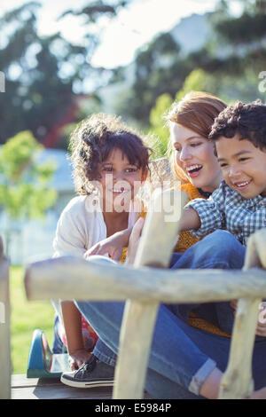 Les élèves et le professeur assis à l'extérieur Banque D'Images