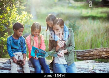 Les élèves et le professeur reading map in forest Banque D'Images