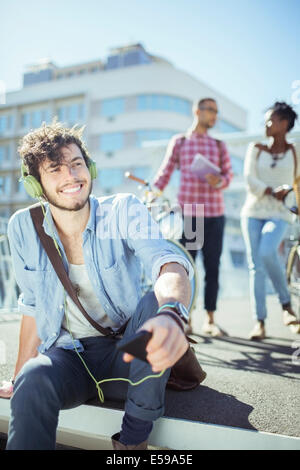 Man listening to mp3 player on city street Banque D'Images