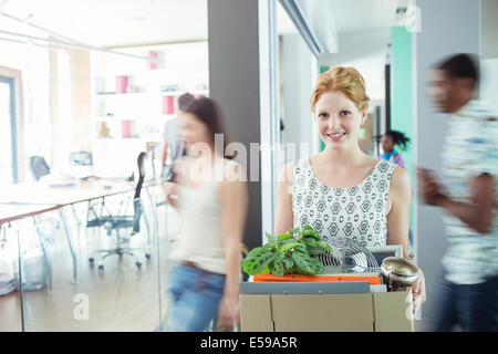 Woman carrying cardboard box in office Banque D'Images