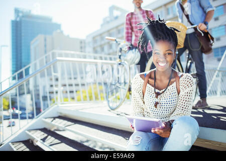 Woman using digital tablet on city street