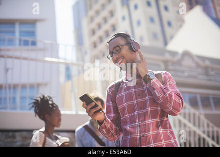 Man listening to mp3 player outdoors Banque D'Images