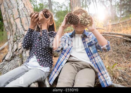 Enfants jouant avec des pommes de pin dans la forêt Banque D'Images
