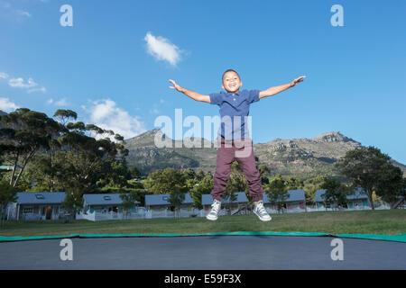 Garçon sautant sur le trampoline à l'extérieur Banque D'Images