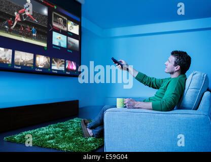 L'homme regardant la télévision dans la salle de séjour Banque D'Images