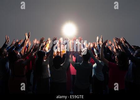 Foule diversifiée avec bras levés autour de lumière vive