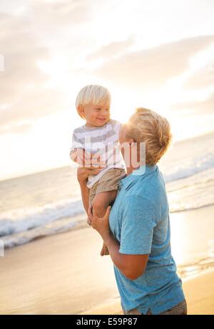 Heureux père aimant et de son fils sur la plage au coucher du soleil Banque D'Images