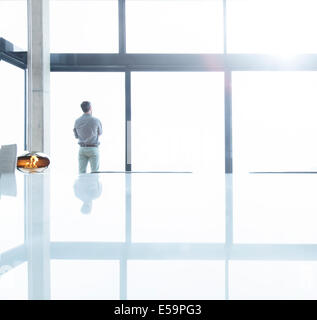 Businessman standing at office window Banque D'Images