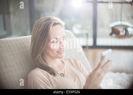 Woman using cell phone on sofa Banque D'Images