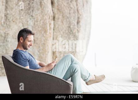 Homme assis dans un fauteuil moderne Banque D'Images