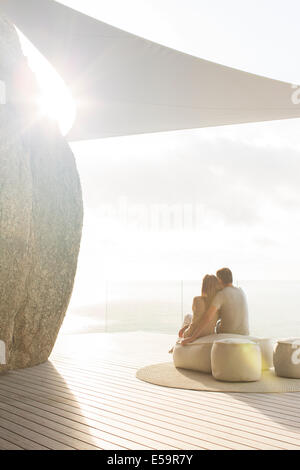 Couple relaxing together sur balcon moderne Banque D'Images