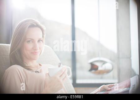 Femme tasse de café sur le canapé Banque D'Images