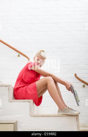 Femme assise sur les marches de la maison moderne Banque D'Images