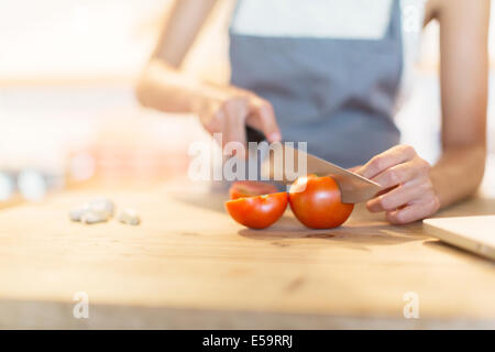 Woman chopping vegetables in kitchen Banque D'Images