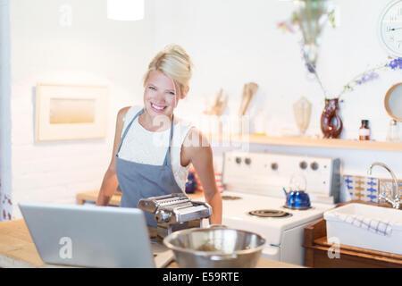 Femme à la cuisson pour ordinateur portable dans la cuisine