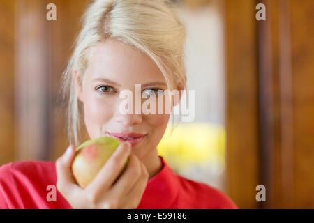 Woman eating apple à l'intérieur Banque D'Images