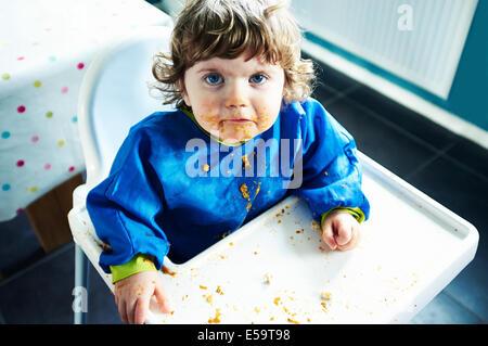 Bébé fille en désordre de manger dans une chaise haute Banque D'Images