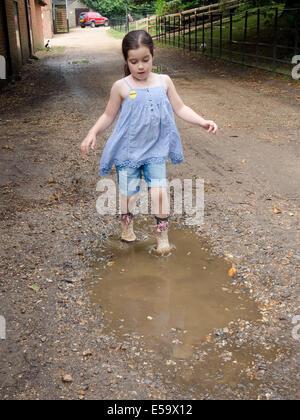Une jeune fille portant des bottes wellington s'éclabousser dans les flaques Banque D'Images