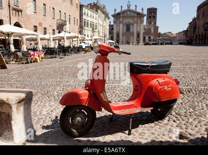 Un vieux scooter rouge garé sur une place pavée de Mantova, Italie Banque D'Images