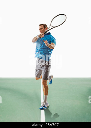 Young man playing tennis on court Banque D'Images