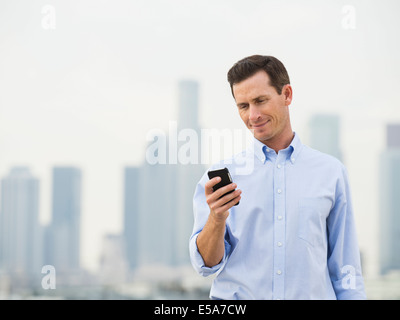 Caucasian businessman using cell phone on urban rooftop Banque D'Images