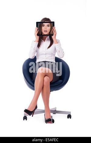 Businesswoman se cacher derrière tablette qui affiche choqué face, Debica, Pologne Banque D'Images