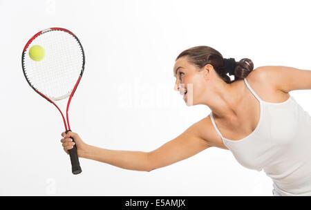Tennis player s'étendant jusqu'à frapper la balle Banque D'Images